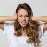 Annoyed stressed woman cover ears feel hurt ear ache pain otitis suffer from loud noise sound headache, irritated stubborn girl deaf hear not listen to noisy music isolated on white studio background (Annoyed stressed woman cover ears feel hurt ear ac